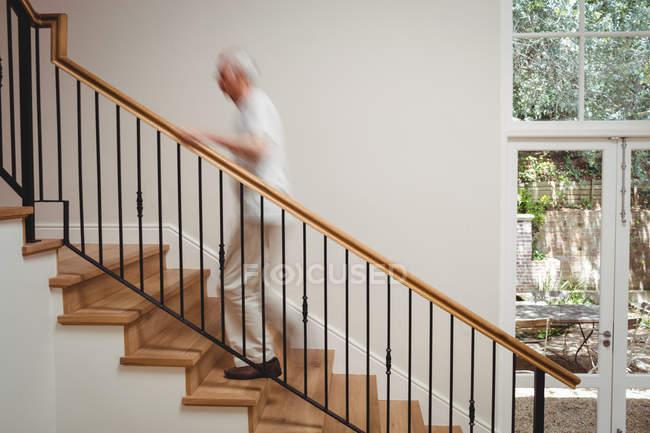 Старший чоловік, піднімання вверх по сходах, тримаючи вдома — стокове фото