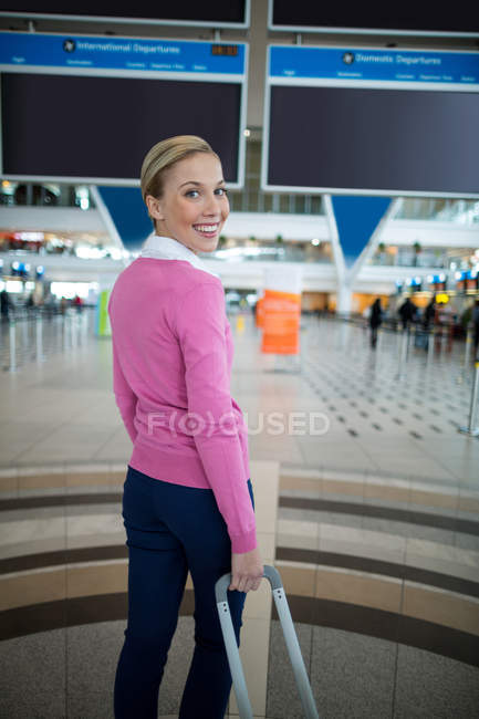Portrait of female commuter standing with luggage at waiting area in airport — Stock Photo