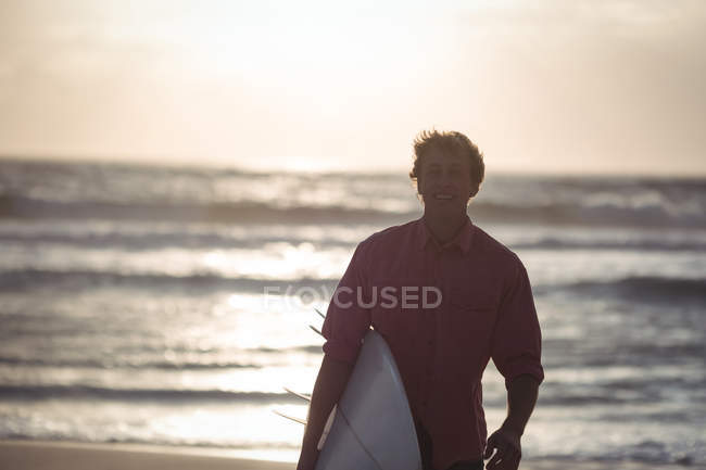 Man carrying surfboard standing on beach at dusk — Stockfoto