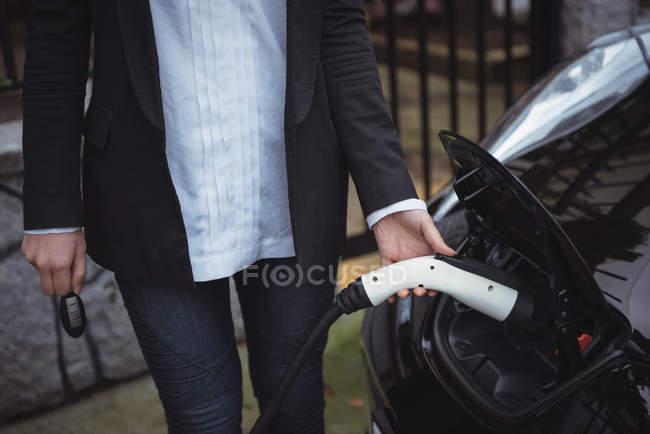 Section médiane de femme recharge voiture électrique à charge conductive pour véhicules — Photo de stock