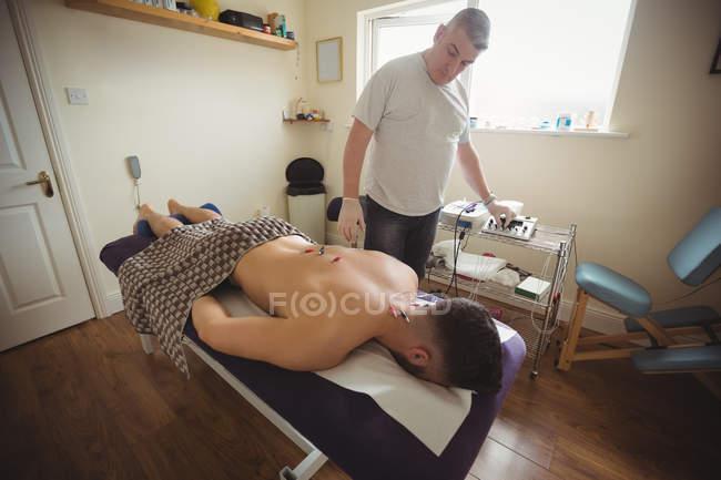 Fisioterapista che esegue aghi elettro-asciutti sulla schiena di un paziente in clinica — Foto stock