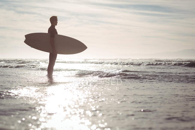 Silhouette of thoughtful surfer standing with surfboard on beach — стоковое фото