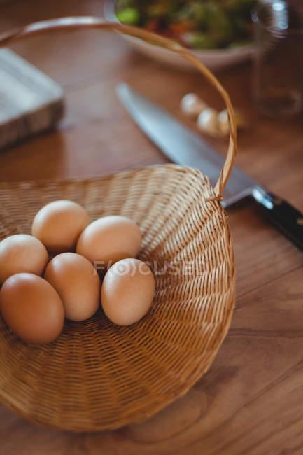 Ovos em cesta de vime em mesa de madeira na cozinha — Fotografia de Stock