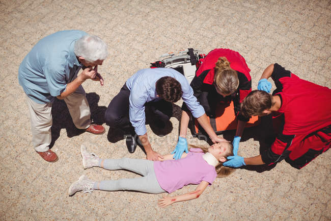 Les ambulanciers examinent une fille blessée dans la rue — Photo de stock