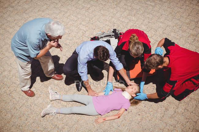 Paramédicos examinando menina ferida na rua — Fotografia de Stock
