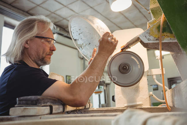 Glassblower polishing and grinding a glassware at glassblowing factory — Stock Photo