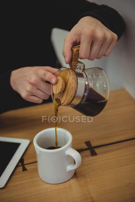 Mi-section de l'homme verser du café de la bouilloire dans la tasse dans le café-restaurant — Photo de stock