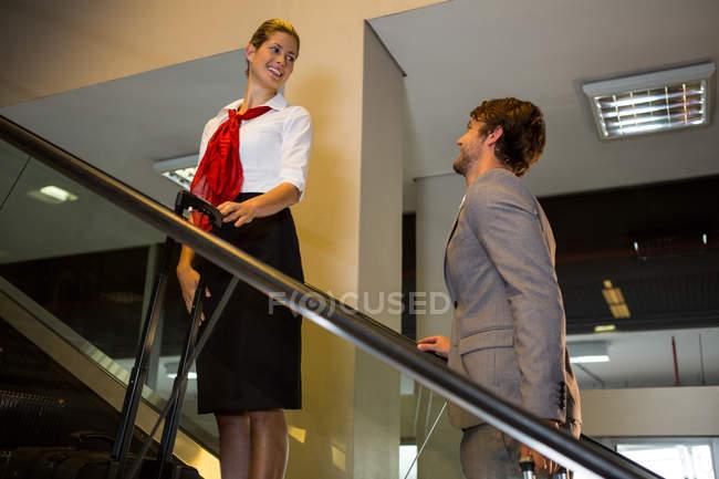 Personnel féminin interagir avec l'homme d'affaires sur l'escalator à l'aéroport — Photo de stock
