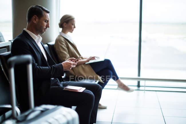 Homme d'affaires utilisant le téléphone portable dans la salle d'attente au terminal de l'aéroport — Photo de stock