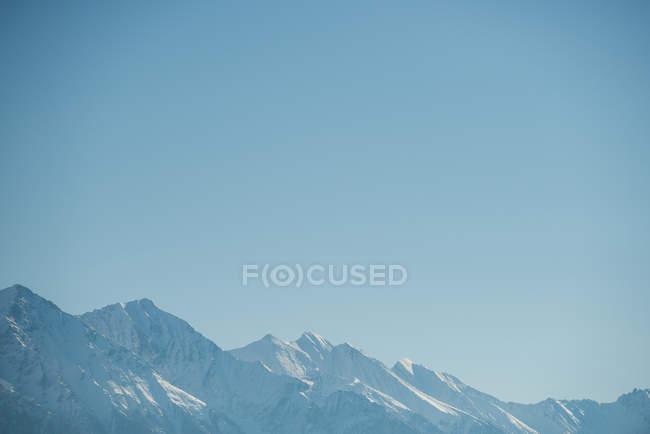 Vue tranquille sur chaîne de montagnes enneigée sur ciel bleu — Photo de stock