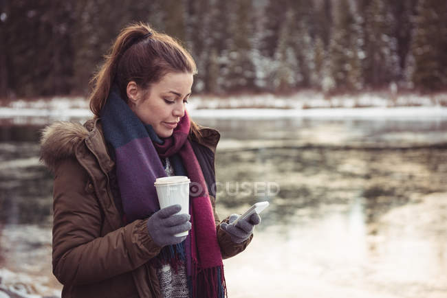 Woman standing on river bank and using mobile phone in winter — Stock Photo