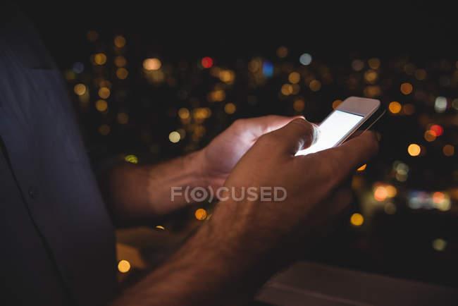 Milieu de l'homme utilisant son téléphone portable dans le balcon la nuit — Photo de stock