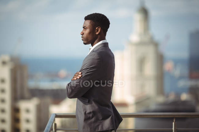 Side view of businessman standing with arms crossed on office terrace — Stock Photo