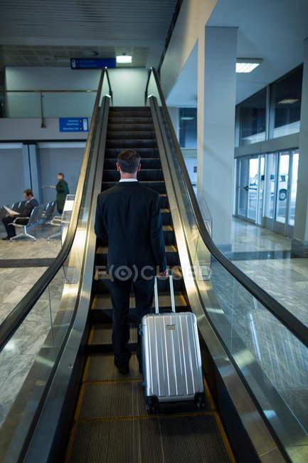 Вид сзади бизнесмена на эскалаторе в аэропорту — стоковое фото