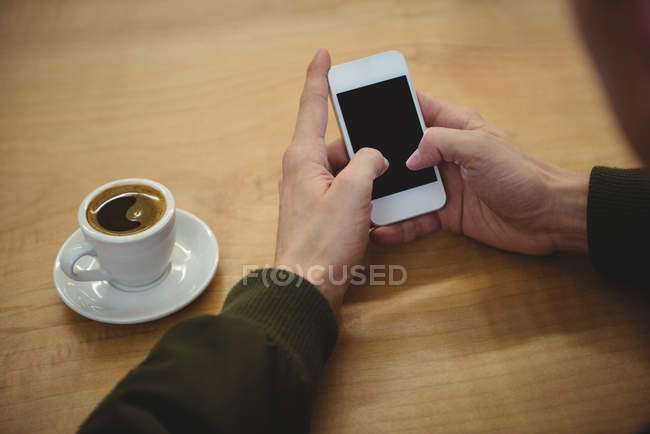 Close-up of male hands using phone on wooden table — Stock Photo
