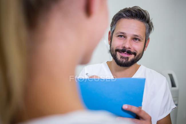Medico che scrive sul rapporto mentre discute con il paziente alla clinica — Foto stock