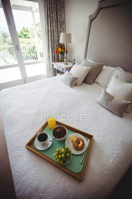 Breakfast tray on bed in bedroom at home — Stock Photo