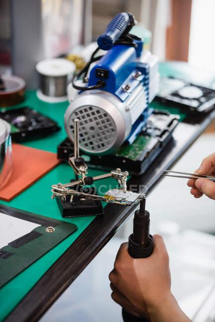 Close-up of man repairing mobile phone in repair centre — Stock Photo
