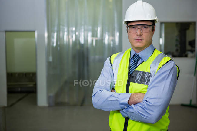 Technician in hard hat and protective eyewear at factory — Stock Photo