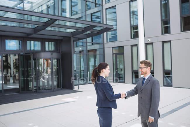 Бізнесмен, потискує руку з колегою за межами Офісна будівля — стокове фото