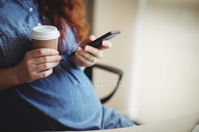 Pregnant businesswoman using mobile phone while having coffee in office — Stock Photo