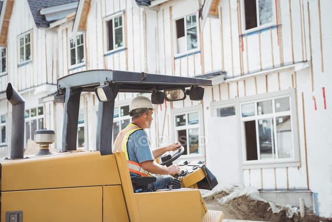 Чоловік працює на будівельному майданчику бульдозер — стокове фото