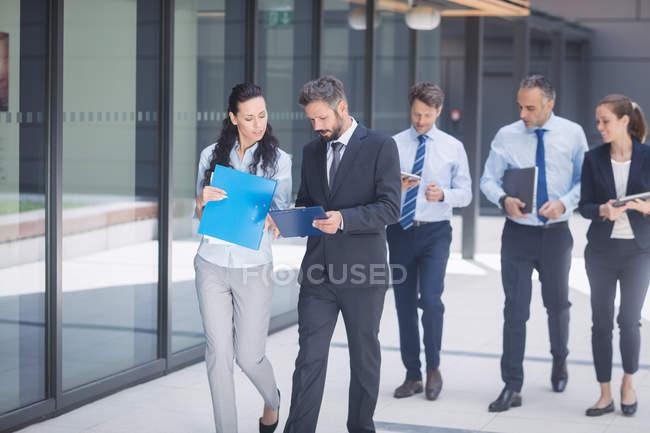 Groupe de gens d'affaires confiants marchant en dehors de l'immeuble de bureaux — Photo de stock