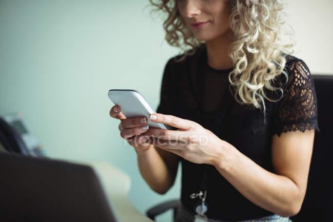 Бізнес-леді за допомогою мобільного телефону в офісі — стокове фото