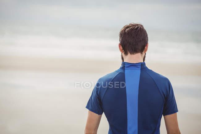 Vista traseira do atleta em pé na praia — Fotografia de Stock