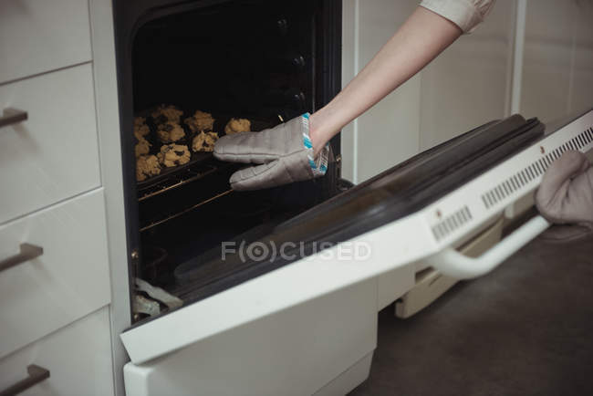 Arm of woman baking cookies in domestic oven — Stock Photo