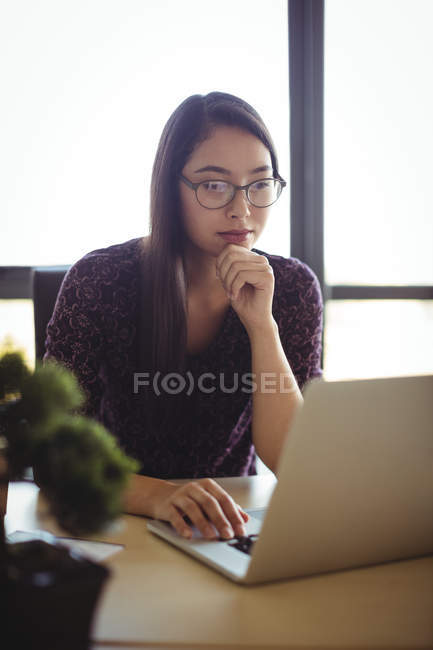 Businesswoman working on laptop in office interior — Stock Photo