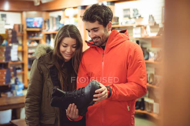 Coppie felici selezionando scarpa insieme in un negozio — Foto stock