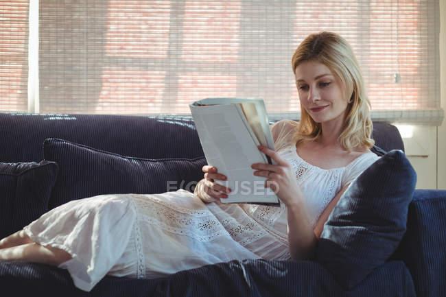 Bella donna seduta sul divano e rivista di lettura in soggiorno a casa — Foto stock