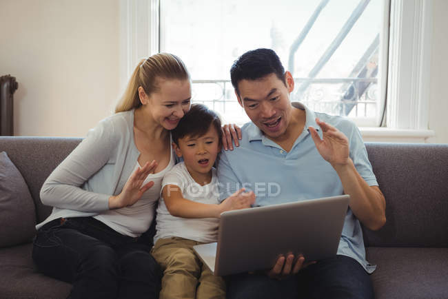 Family having video chat on laptop in living room at home — Stock Photo
