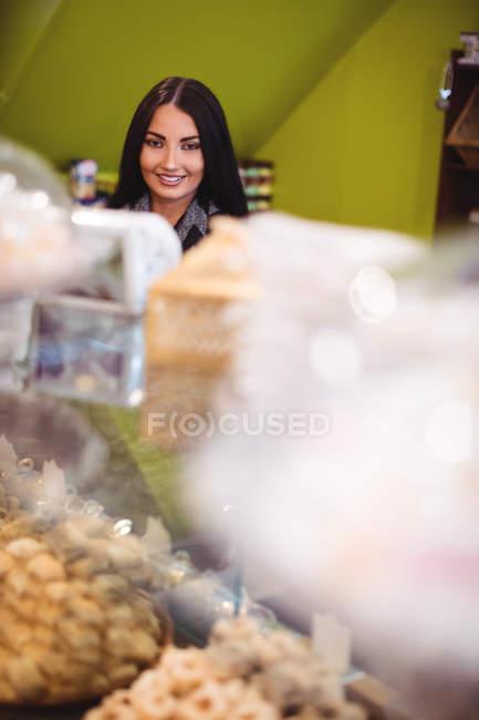 Retrato de una hermosa mujer de pie en la tienda de dulces turcos - foto de stock