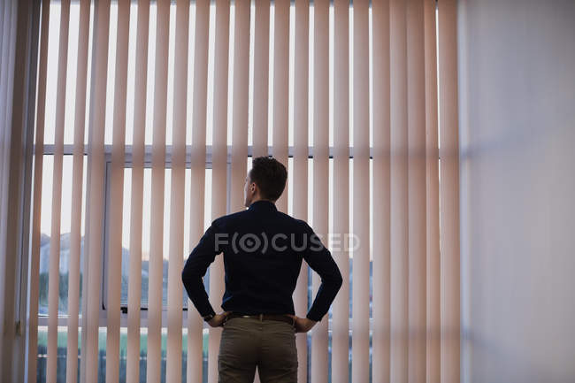 Задній вид на людину, стоячи з руки на стегнах поблизу штори — стокове фото