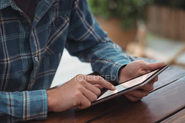 Primer plano de un hombre sentado en el escritorio y usando tableta digital en casa - foto de stock