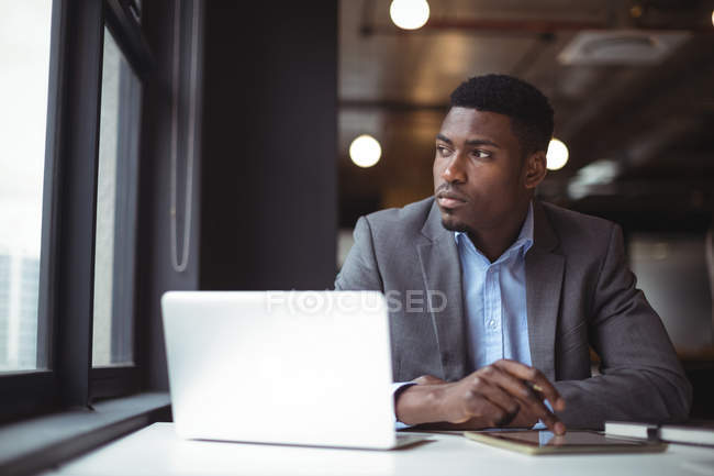 Thoughtful businessman looking at window in office — Stock Photo