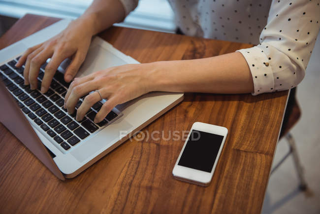 Hands of businesswoman using laptop in the cafe — Stock Photo