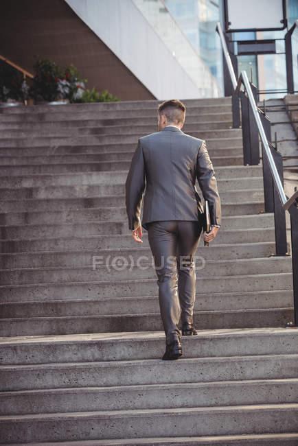 Vue arrière de l'homme d'affaires avec un journal grimper les escaliers au bureau — Photo de stock