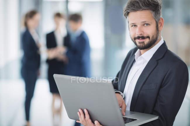 Portrait d'un homme d'affaires debout au bureau et utilisant un ordinateur portable — Photo de stock