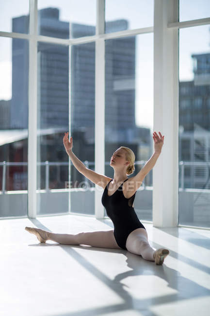 Ballerina performing leg split in ballet studio — Stock Photo