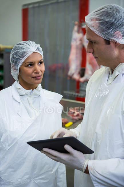 М'ясників, обговорюючи над цифровий планшет на заводі м'яса — стокове фото