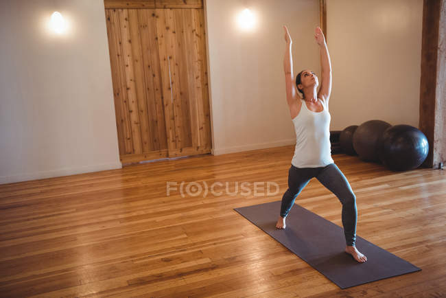 Mid adult woman practicing yoga warrior pose in fitness studio — Stock Photo