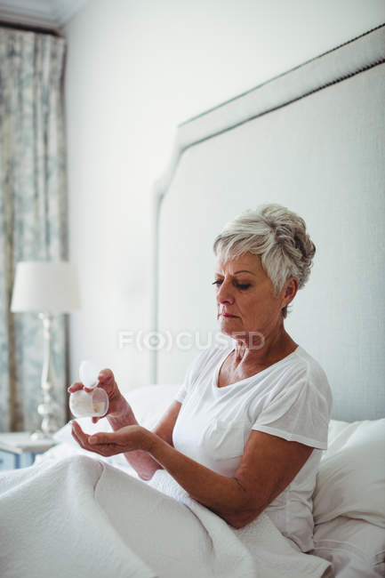 Senior woman taking medicine in bedroom at home — Stock Photo