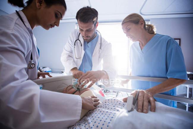 Команда врачей, надевает кислородную маску лицом мужского старших пациентов в больнице — стоковое фото