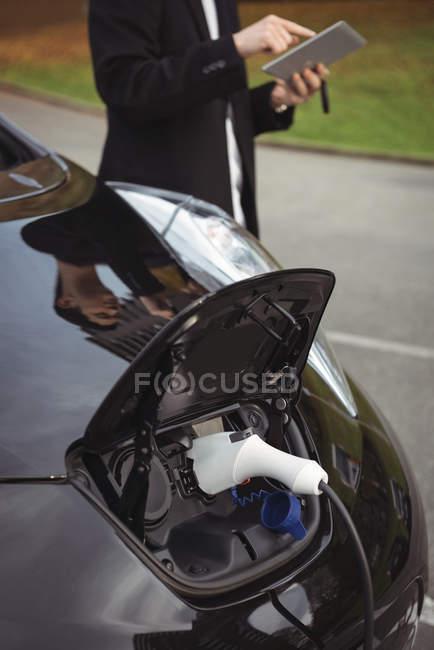 Voiture chargée avec chargeur de voiture électrique à la station de recharge du véhicule électrique — Photo de stock