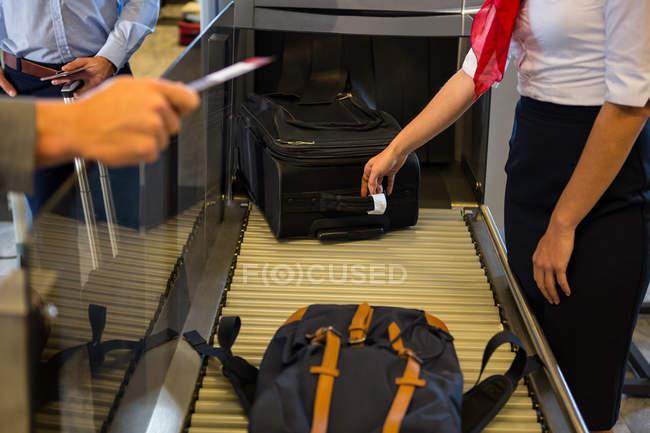 Женского персонала, проверки багажа пассажиров на конвейер в аэропорту — стоковое фото
