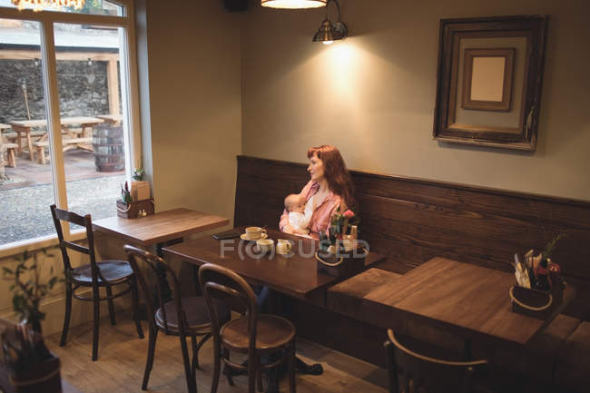 Mutter stillt Baby im Café-Innenraum — Stockfoto