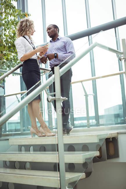 Führungskräfte diskutieren in der Nähe von Treppen im Büroflur — Stockfoto